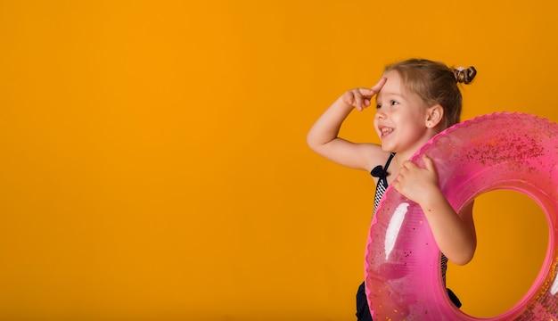 Śmieszna mała dziewczynka w pasiastym stroju kąpielowym trzyma różowy nadmuchiwany okrąg i patrzy w bok na żółtym tle z miejscem na tekst