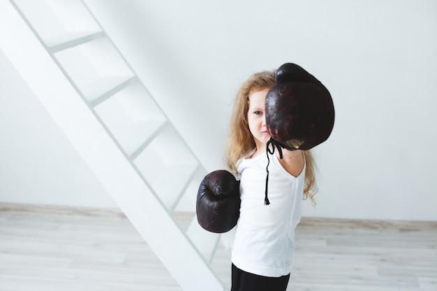 Śmieszna mała dziewczynka w rękawicach bokserskich. zwycięzca.