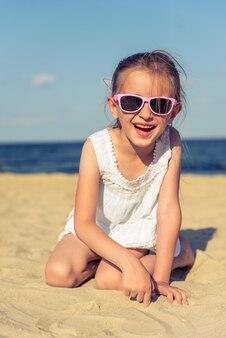 Śmieszna mała dziewczynka w słońc szkłach jest przyglądającym kamerą.