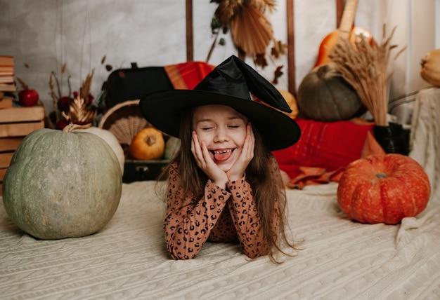 Śmieszna mała dziewczynka w stroju wiedźmy leży z dużymi dyniami w scenerii