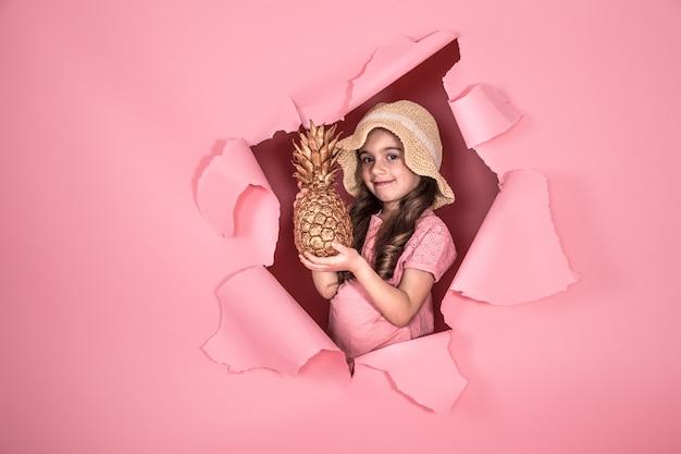 Śmieszna mała dziewczynka z ananasem na kolorowym tle