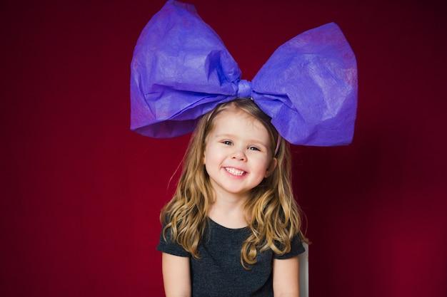 Śmieszna mała dziewczynka z dużą kokardą na głowie