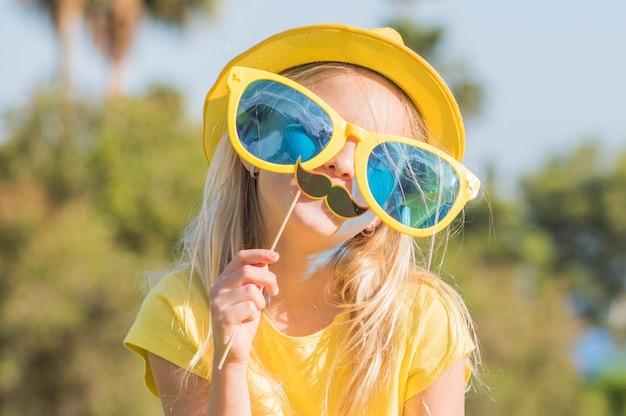 Śmieszna mała dziewczynka z papierową maską. urodziny dla dzieci, zabawa w okresie letnim.