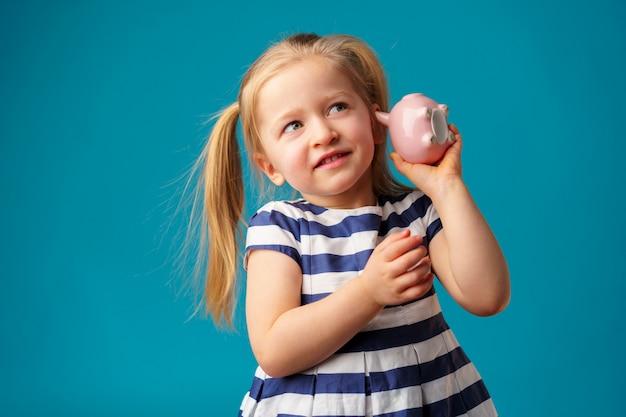 Śmieszna mała dziewczynka z prosiątko banka moneybox portretem