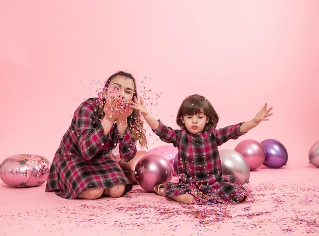 Śmieszna mama i dziecko siedzi na różowej ścianie. mała dziewczynka i matka ma zabawę z balonami i confetti