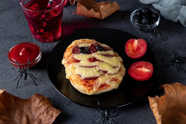 Śmieszna mini pizza mumia z kiełbasą i serem na imprezę halloween, podana z czarnymi oliwkami, keczupem i napojami na ciemnym tle