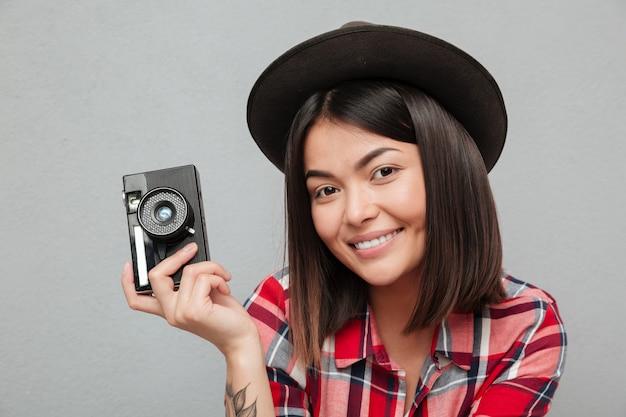 Śmieszna młoda azjatykcia kobieta odizolowywająca nad szarości ściany mienia kamerą.