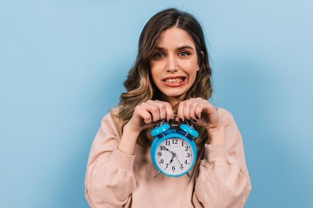 Śmieszna młoda dama pozuje z dużym zegarem