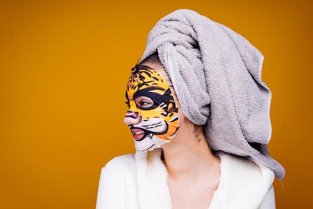 Śmieszna młoda dziewczyna z ręcznikiem na głowie uśmiechnięta, na twarzy maska z pyskiem zwierzęcia