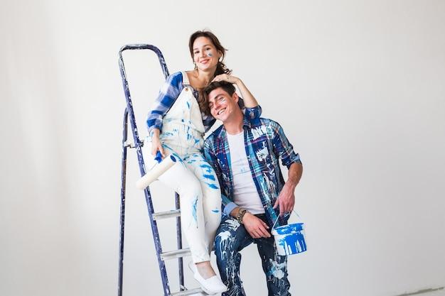 Śmieszna młoda kobieta i mężczyzna stojący na drabinie.