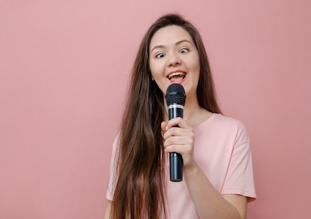Śmieszna młoda kobieta śpiewa do mikrofonu na różowych, zezujących oczach, żart
