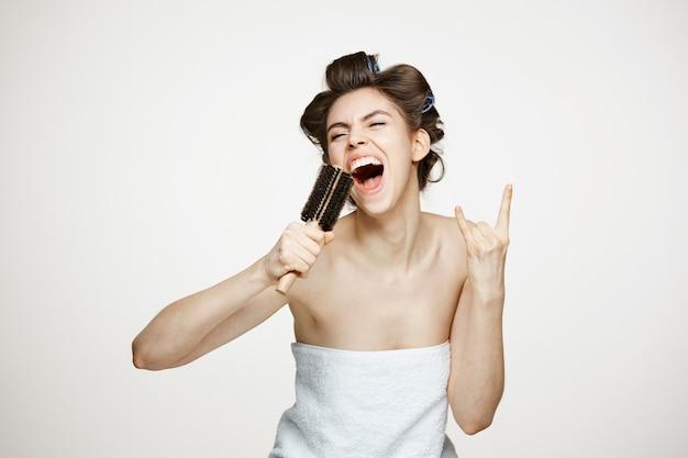 Śmieszna młoda kobieta w curlers i ręcznik do włosów śpiewa w grzebieniu. uroda i spa.