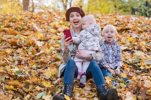 Śmieszna młoda matka i dwoje dzieci siedzą w jesiennych liściach w parku