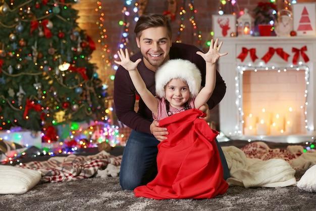 Śmieszna młodsza siostra w worku świętego mikołaja, która zaskakuje starszego brata na świątecznym tle