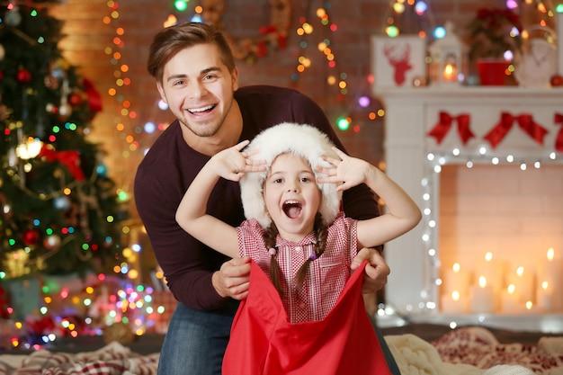 Śmieszna młodsza siostra w worku świętego mikołaja zaskakuje starszego brata w boże narodzenie