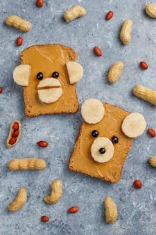 Śmieszna niedźwiedzia i małpy twarzy kanapka z masłem orzechowym, bananem i czarną porzeczką, arachidy, widok z góry