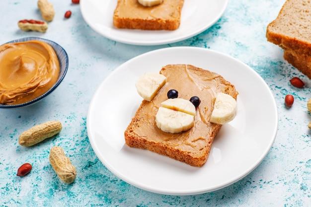 Śmieszna niedźwiedzia i małpy twarzy kanapka z masłem orzechowym, bananem i czarną porzeczką, widok z góry
