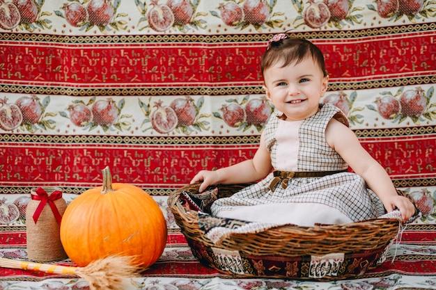 Śmieszna ormiańska dziewczynka siedzi w dużym słomkowym koszu i śmieje się obok dyni
