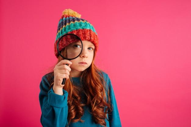 Śmieszna poważna dziewczyna patrzeje przez powiększać - szkło przy kamerą
