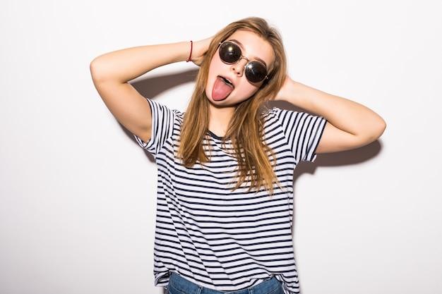 Śmieszna przypadkowa nastolatek kobieta jest ubranym moda okularów przeciwsłonecznych gestykulować odizolowywam na białej ścianie