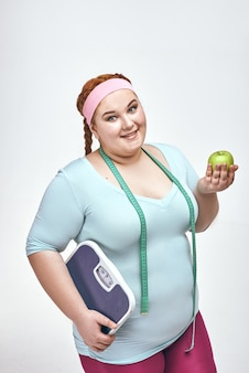 Śmieszna pulchna kobieta trzyma jabłko i wagę