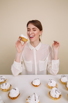 Śmieszna radosna młoda kobieta je ciasta i ma zabawę