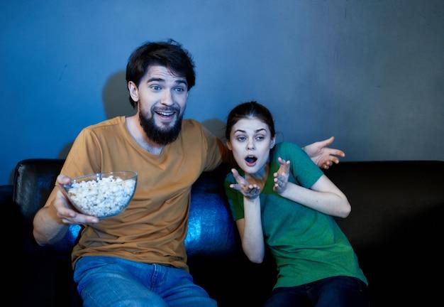 Śmieszna rodzina siedzi w domu na kanapie oglądając filmy popcornowe emocje