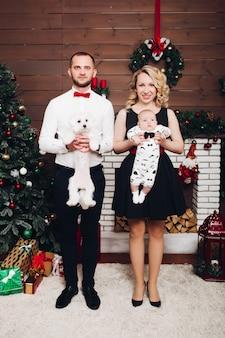 Śmieszna rodzina stoi blisko kominka mienia psa, syna w rękach i ono uśmiecha się