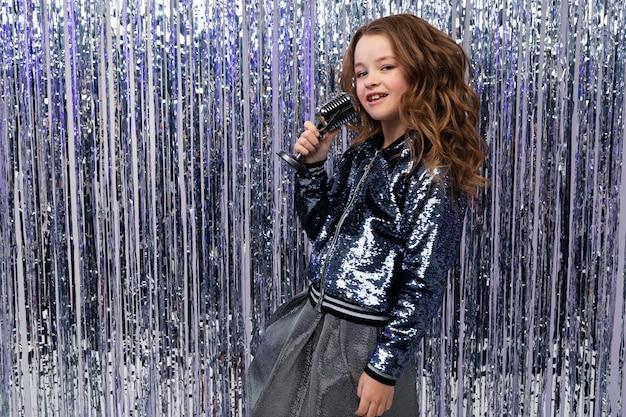 Śmieszna rozochocona stylowa dziewczyna z mikrofonem w jej rękach na błyszczącej świecidełku ścianie z pustą przestrzenią