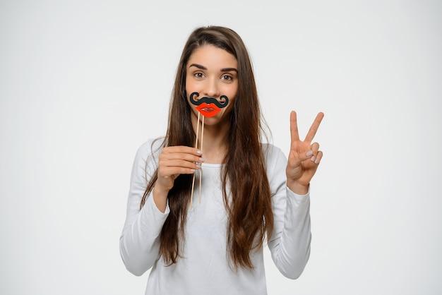 Śmieszna śliczna kobieta z sfałszowanymi wargami i wąsem, pokazuje pokój