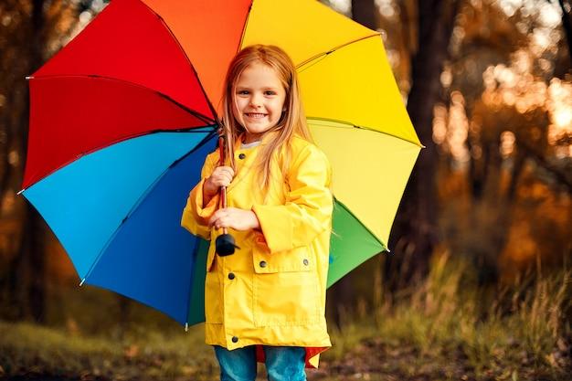 Śmieszna śliczna maluch dziewczyna jest ubranym wodoodpornego płaszcz z kolorowym parasolem