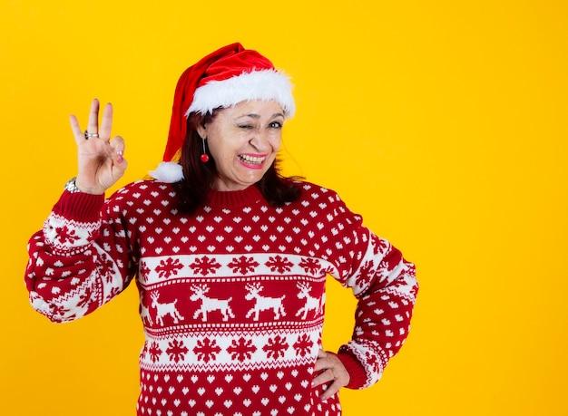 Śmieszna starsza kobieta ok gest, boże narodzenie z czerwonym santa hat