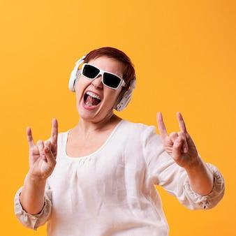 Śmieszna starsza kobieta słucha muzykę rockową
