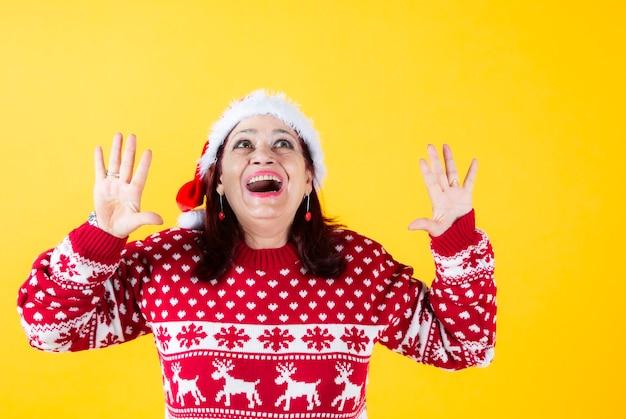 Śmieszna starsza kobieta śmiejąca się na boże narodzenie z czerwonym santa hat