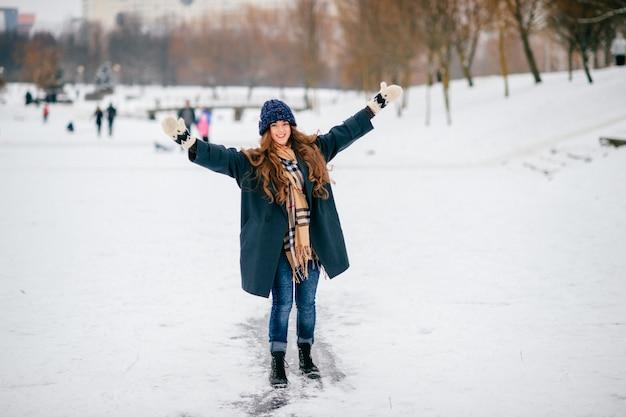 Śmieszna stylowa kobieta jedzie lodowego ślad w zima parku.