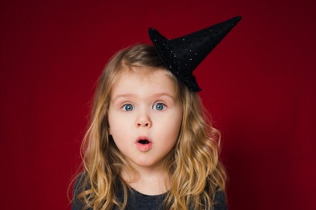 Śmieszna twarz dziewczyny w kapelusz czarownicy