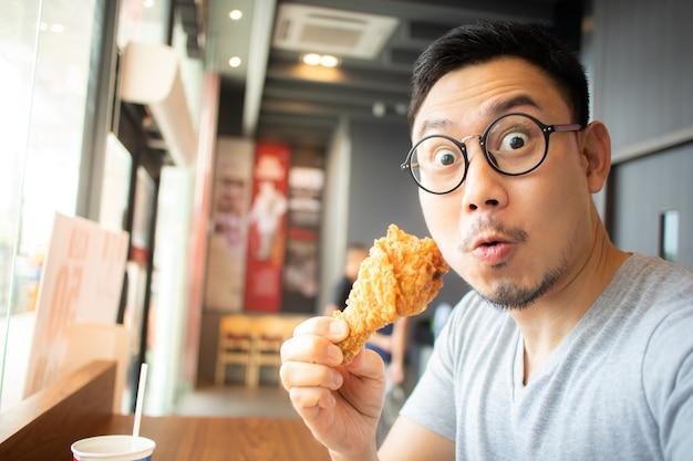 Śmieszna twarz mężczyzna je smażonego kurczaka w kawiarni franczyzy.