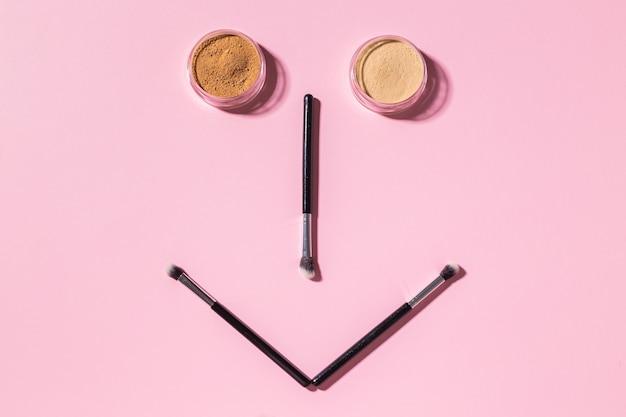 Śmieszna twarz z pędzlami do makijażu i pudrem mineralnym na różowym tle z widokiem z góry na miejsce na kopię