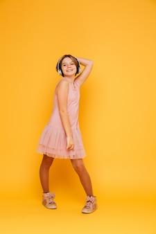 Śmieszna uśmiechnięta dziewczyna w hełmofonów pozować odizolowywam nad kolorem żółtym