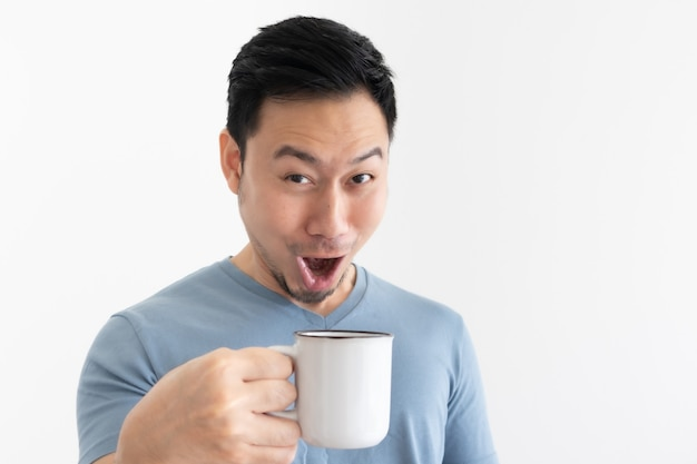 Śmieszna wow twarz mężczyzny w niebieskiej koszulce pije kawę z białego kubka.