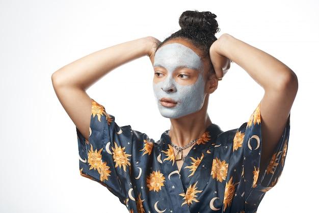 Śmieszna yong dziewczyna z glinianą piękno maską na skóra odosobnionym modelu