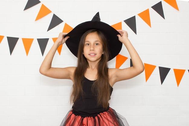 Śmieszna zabawna dziewczyna w kapeluszu i kostiumie wiedźmy na halloween trzyma pola kapeluszy