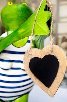 Śmieszna zielona żaba trzyma drewniane serce z miejscem na tekst. obchody walentynki.