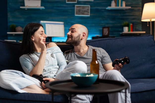 Śmieszna zrelaksowana para siedzi na kanapie relaksując się w nocy, śmiejąc się, bawiąc się
