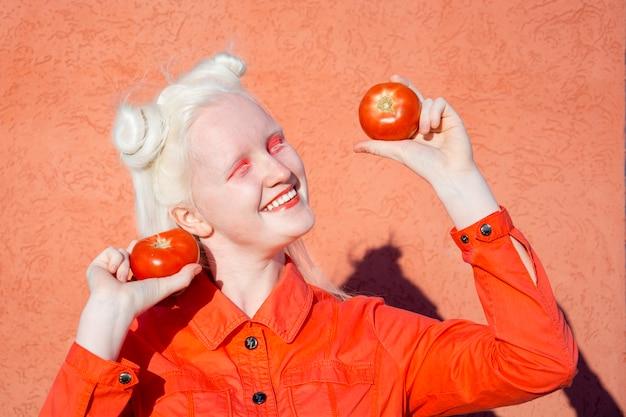 Śmieszne albinos młoda kobieta w czerwonej bluzce na czerwonym tle. trzyma przed oczami dwa czerwone pomidory i uśmiecha się szeroko. kopiuj przestrzeń