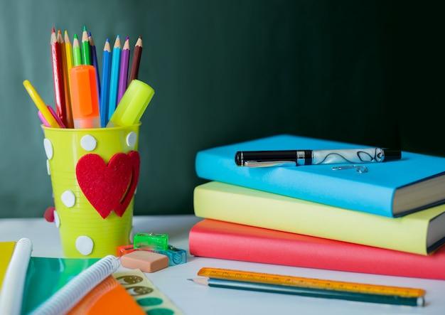 Śmieszne biurko dla nauczycieli pełne kolorowych przyborów szkolnych i zielonej tablicy w tle