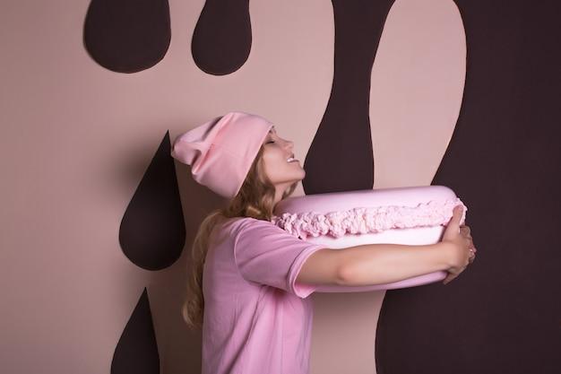 Śmieszne blond kobieta w różowej koszulce i czapce, zabawy z dużym ciastem makaronik. koncepcja wakacji