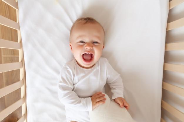 Śmieszne blond słodkie dziecko, leżąc i śmiejąc się w białym łóżku dziecka