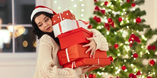 Śmieszne boże narodzenie santa kobieta z prezentami w domu