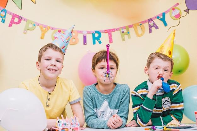 Śmieszne chłopaki i dziewczyna na imprezie birtday